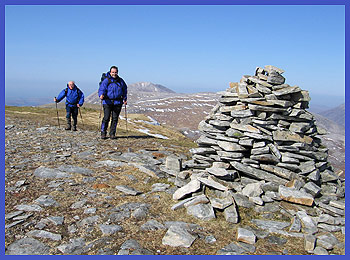 Andrew and Barry stride up to the summit cairn of Meall Horn, with Foinavon glowing in the sun behind